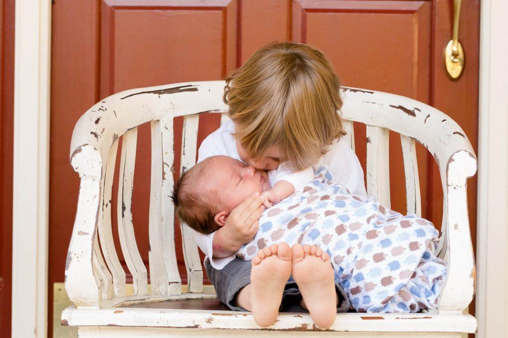 Chłopiec trzyma na kolanach swoje maleńkie rodzeństwo