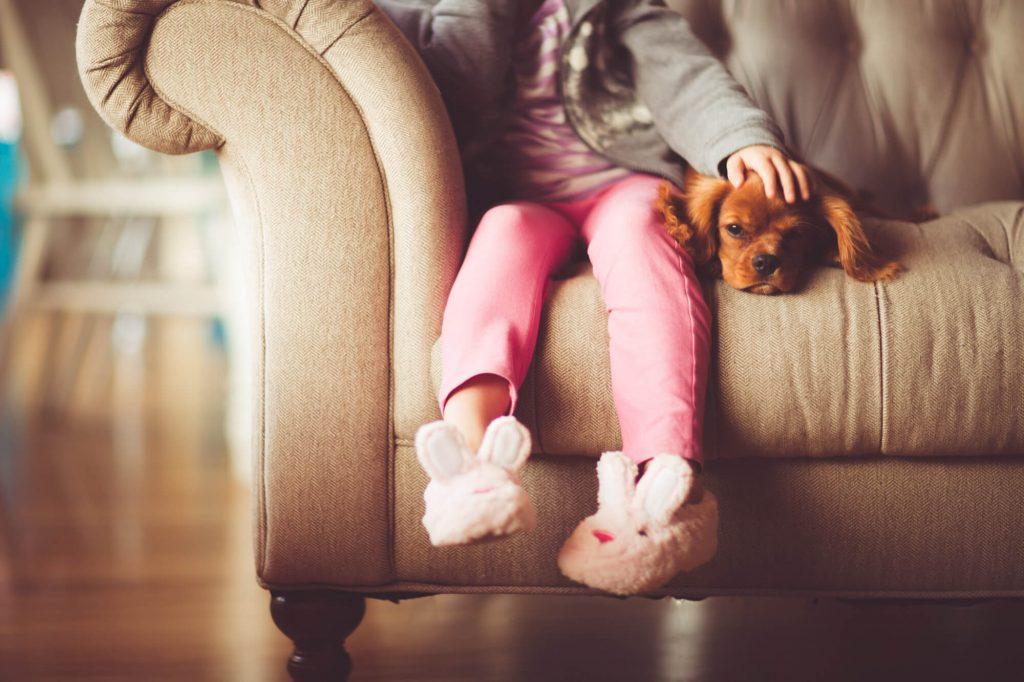 Dziecko siedzi na kanapie z psem