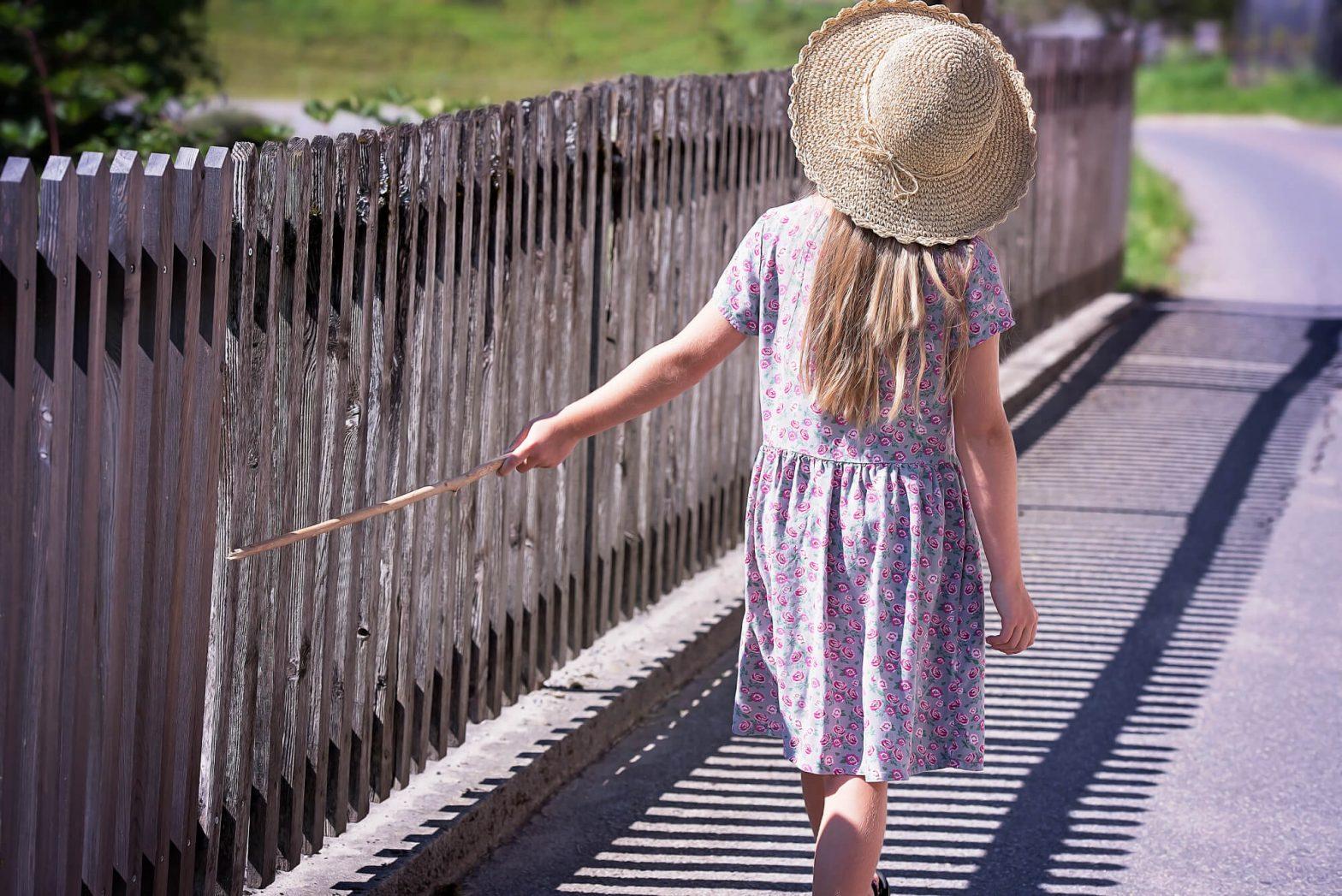 Dziewczynka idzie drogą z patykiem