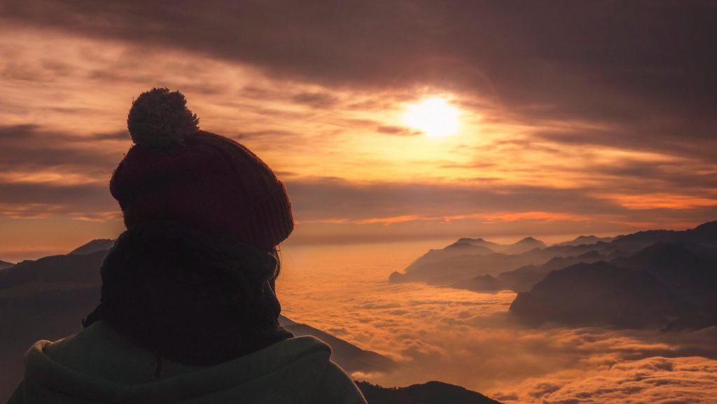 Szczyty gór ponad chmurami o zachodzie słońca