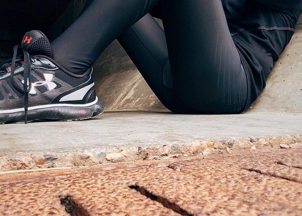 Osoba w sportowym stroju siedzi na ziemi
